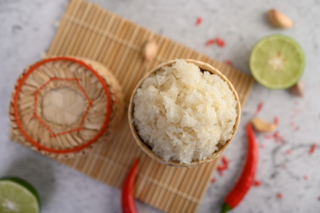 Thai sticky rice in a woven bamboo basket on a wooden panel with chilies, lime, and garlic Free Photo