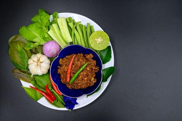 フラットスタイルの黒い背景に野菜の多くとタイ風チリソース Premium写真