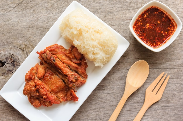 Thai style fried chicken with red spicy sauce and sticky rice isolated on wooden table Premium Photo
