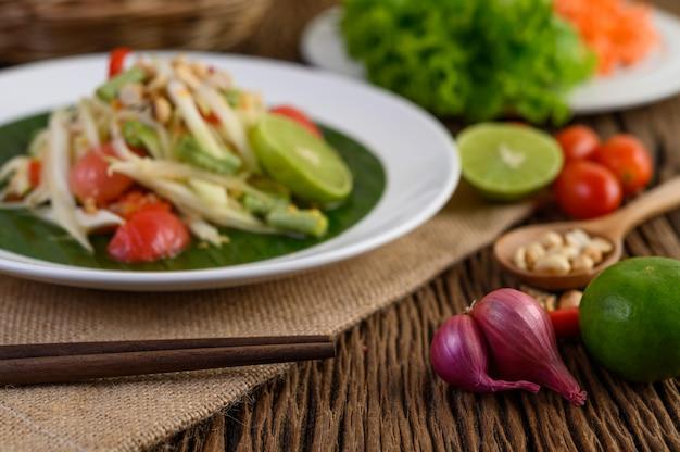Cibo piccante in stile tailandese, concetto di cibo som tum, decorazione di oggetti di scena aglio, limone, arachidi, pomodori e scalogni sul tavolo di legno Foto Gratuite