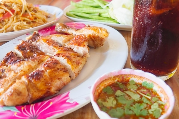 Thai style spicy meal, chicken grilled with spicy papaya salad and cold drink Free Photo