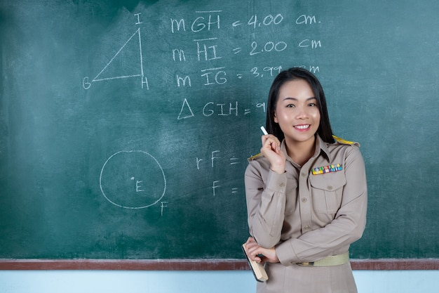 Thai teacher in official outfit  teaching in front of  backboard Free Photo