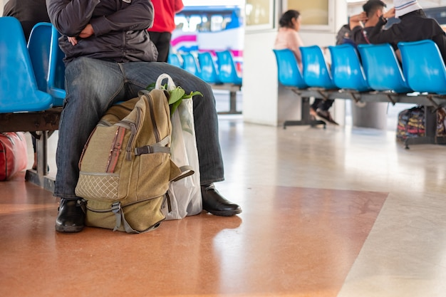 Thai traveler with bags sit waiting for bus in terminal at bus staion in bangkok, thailand. Premium Photo