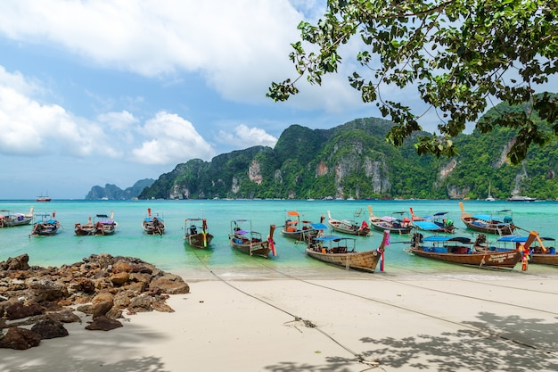 Thailand beach seascape with  steep limestone hills and traditional longtail boats parking Premium Photo