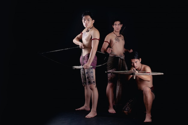 Thailand men warriors posing in a fighting stance with weapons Free Photo
