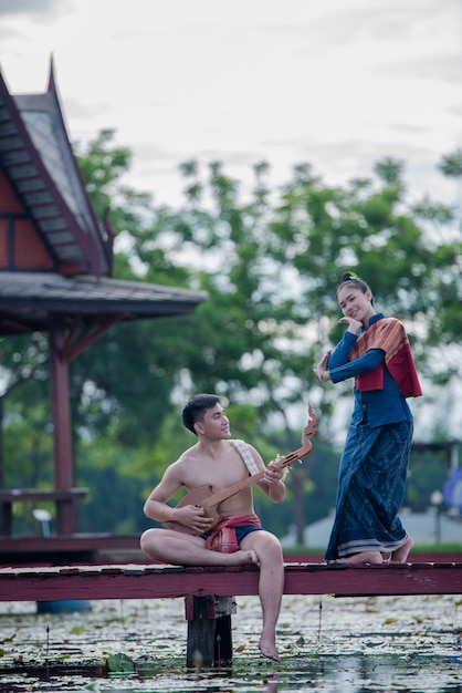 Thailand women and man in national costume with guitar pin ( plucked stringed instrument) Free Photo