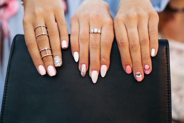 黒のハンドバッグにthairの指を保持している彼女のスタイリッシュなマニキュアを示す女の子。 Premium写真