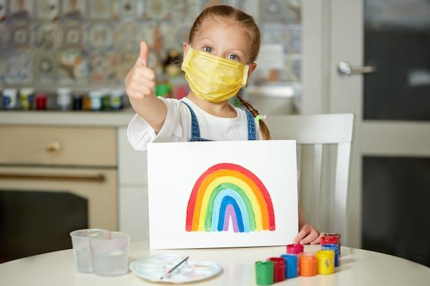 Nhsに感謝します。 covid-19検疫中に自宅で虹を描いている防護マスクの子供。コロナウイルスcovid-19の発生。 Premium写真