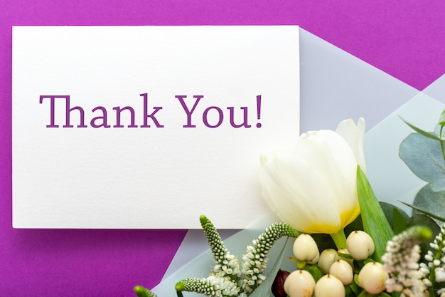 Thank you card in bouquet of roses, tulips, eucalyptus on purple surface Premium Photo