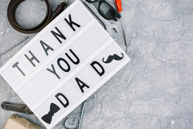 Thank you dad inscription on tablet near male accessories Free Photo
