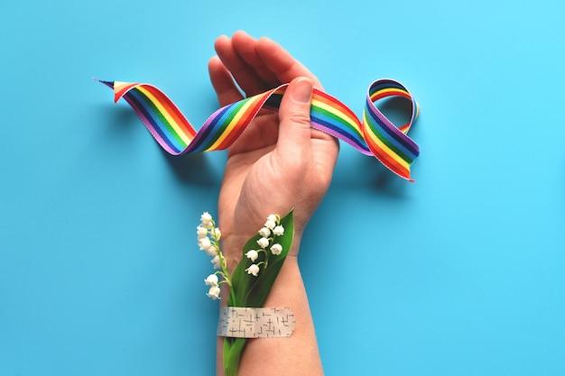 医師と看護師に感謝します!医療援助パッチを取り付けたカモミールの花とグラスのブーケを持つ成熟した女性の手でレインボーリボン Premium写真