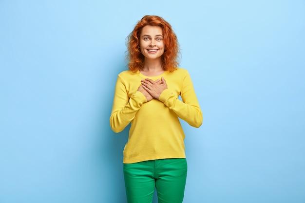 サポートありがとうございます。ゴージャスな赤毛の女性が触れられ、感謝の気持ちで胸に手を押し、助けに感謝します 無料写真