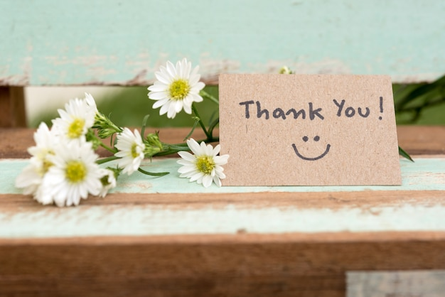 Thank you note with smile face and flower cluster Premium Photo