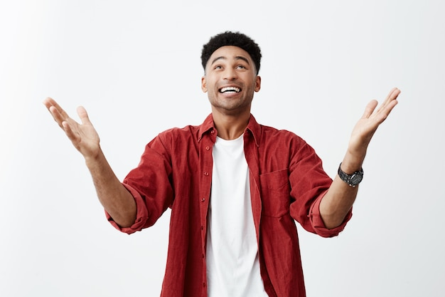 Thanks god. close up of happy young attractive black-skinned man with afro haircut in casual fashionable outfit spreading hands, being happy that he finally won prize in competition. Free Photo