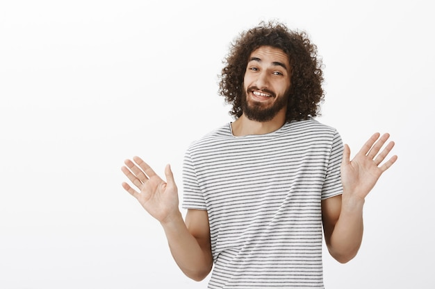 Thanks but i pass. carefree good-looking eastern guy with curly hair, raising palms and waving them near chest in rejection gesture, smiling awkwardly and denying involvement Free Photo