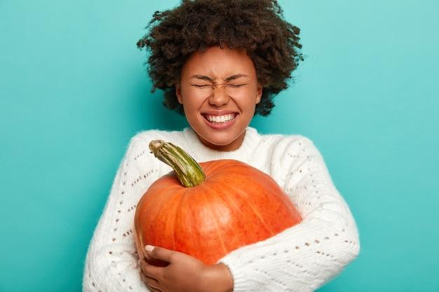 추수 감사절과 가을 시간 개념. 즐거운 어두운 피부 여자가 가을 작물, 큰 주황색 호박을 포용 무료 사진