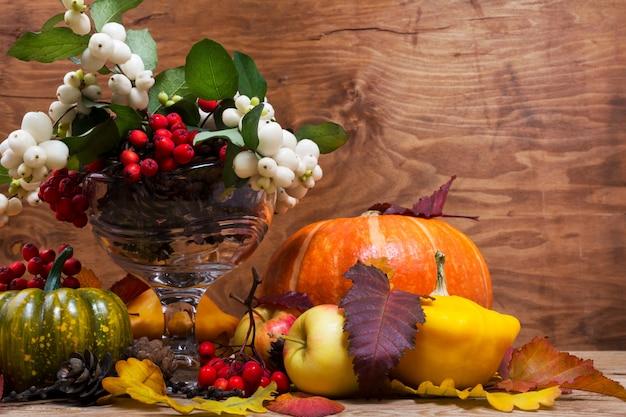 ガラスの花瓶、コピースペースにスノーベリーとナナカマドの感謝祭の配置 Premium写真
