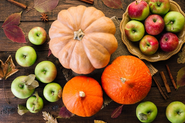 Thanksgiving background, pumpkins, apples and spices on a wooden table Premium Photo