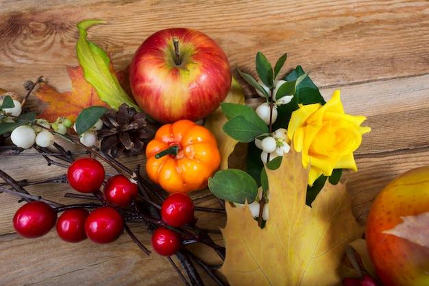 黄色いバラ、赤と白の果実と感謝祭の背景 Premium写真
