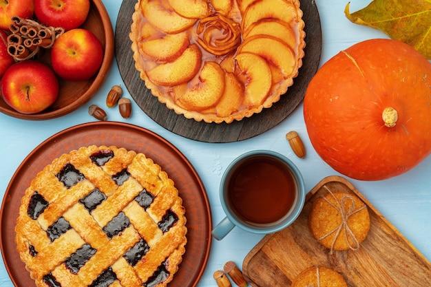 感謝祭のベリーとリンゴの木製の表面、上面図、コピースペースのさまざまなパイ Premium写真