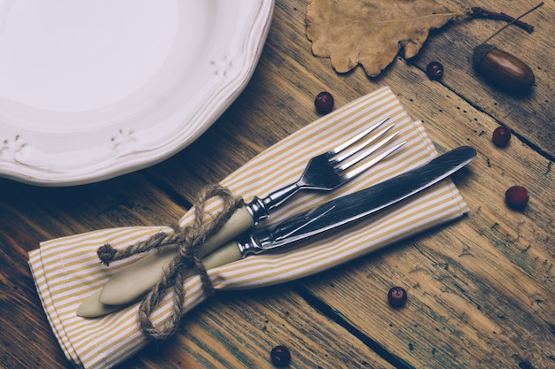 Thanksgiving dinner concept background: white plate, spoon and fork on a wooden rustic table with autumn leaves, red berries and acorns Premium Photo