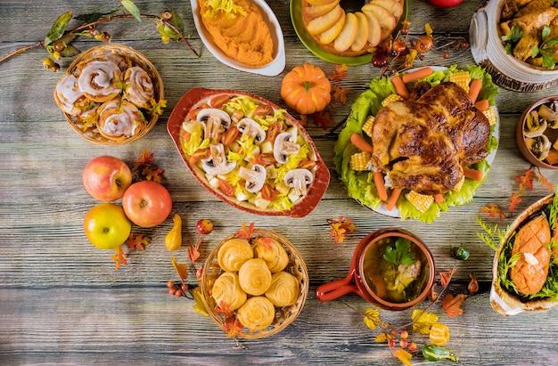 Thanksgiving dinner. roasted turkey with apple pie, pumpkin and cinnamon rolls. Premium Photo