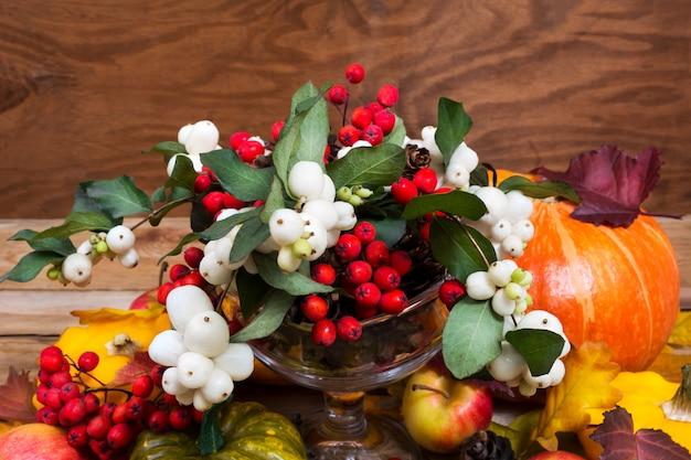 感謝祭のスノーベリー、ナナカマドの果実、カボチャ、リンゴテーブルのセンターピース Premium写真
