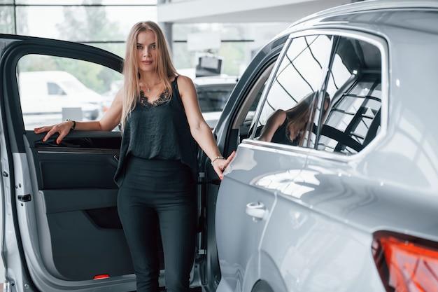 Вот так выглядит успех. девушка и современная машина в салоне. днем в помещении. покупка нового автомобиля Бесплатные Фотографии