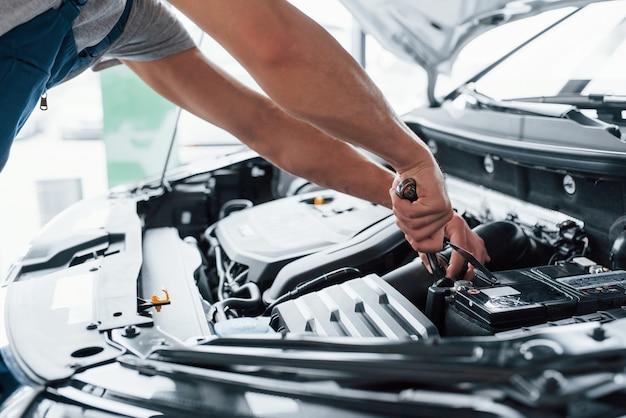 Это нужно подзарядить. процесс ремонта автомобиля после аварии. человек, работающий с двигателем под капотом Бесплатные Фотографии
