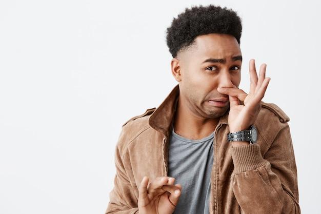 いいにおいがする。市内のゴミ捨て場からの嫌なにおいからの広告を感じて、指で鼻を閉じてアフロの髪型を持つ若い変な浅黒い肌の男の肖像画を閉じます。 無料写真