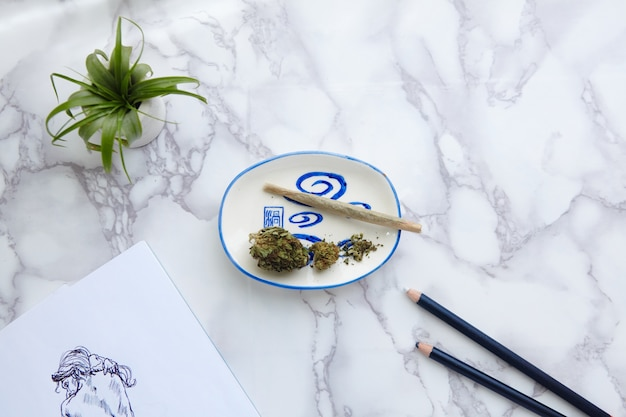 Thc cbd marijuana joint and flowers on ash tray with nude illustration on drawing pad Free Photo