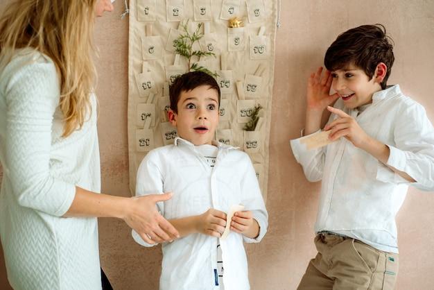 壁に掛かっているアドベントカレンダー。子供のための贈り物の驚き。 2人の感情的な男の子 Premium写真