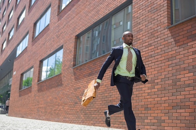 Африканский мужчина как черный бизнесмен с портфелем работает на городской улице на фоне красной кирпичной стены Бесплатные Фотографии