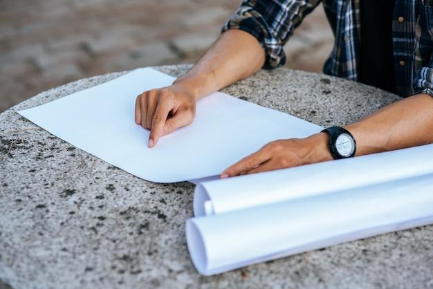 建築家は座って建築計画を調べました。 無料写真