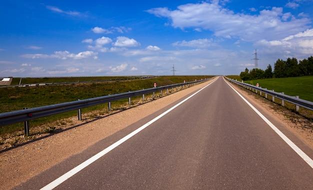 Асфальтированная дорога - небольшая асфальтированная дорога, находящаяся в сельской местности. Premium Фотографии