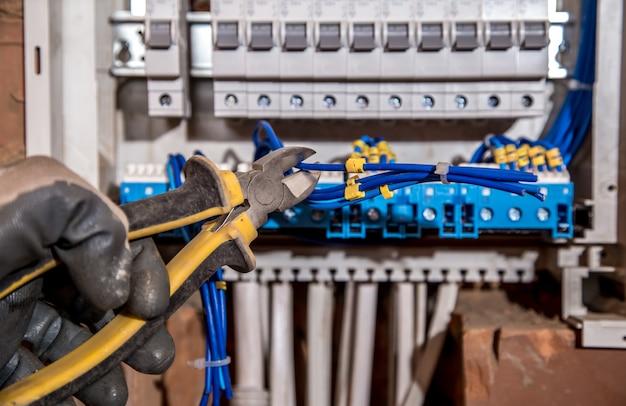電気パネルの組み立て、電気技師の仕事、ワイヤーと回路ブレーカーを備えたロボット Premium写真