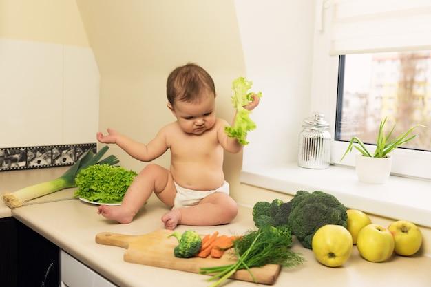 おむつの赤ちゃんは台所のテーブルに座っています。子供が遊んで、新鮮な有機野菜や果物を楽しんでいます。 Premium写真