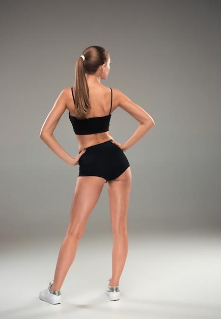 灰色のポーズ筋肉の若い女性アスリートの背面図 無料写真