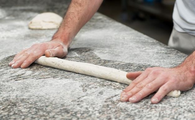 Пекарь готовит хлебное тесто Premium Фотографии