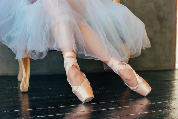 클래식 의자에 앉아 Pointe Shous의 발레리나 발레 댄서 프리미엄 사진