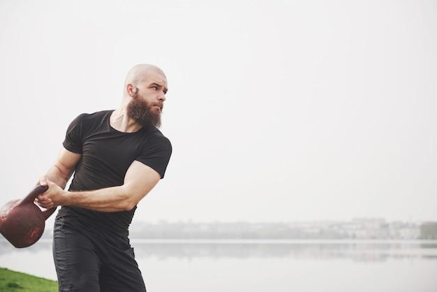 Бородатый молодой человек занимается спортом на открытом воздухе Бесплатные Фотографии