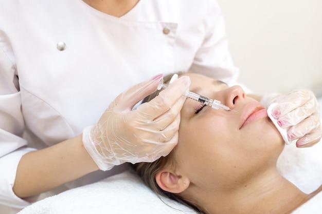 美容師は患者の唇の増強を行います Premium写真