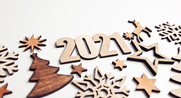 白い机の上に小さな木製の装飾と木製の数字2021がたくさんある美しいクリスマスの背景。 Premium写真