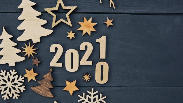 木製の机の上に小さな木製の装飾と木製の番号2021がたくさんある美しいクリスマスの背景。 Premium写真
