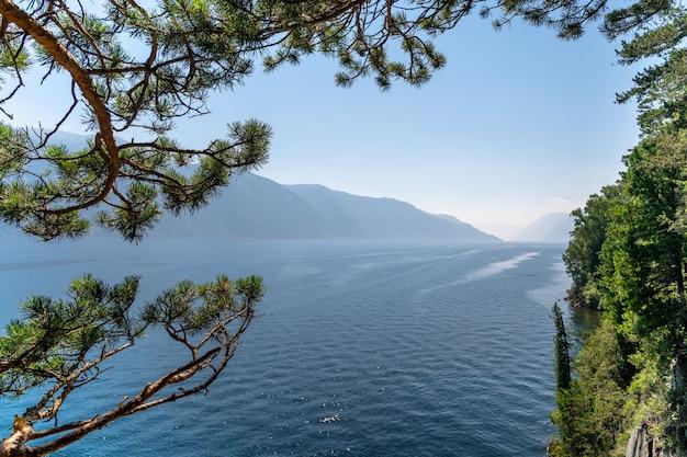 Лодка идет по горному озеру. красивое озеро в горах. кедровые ветви нависают над озером. путешествия Premium Фотографии