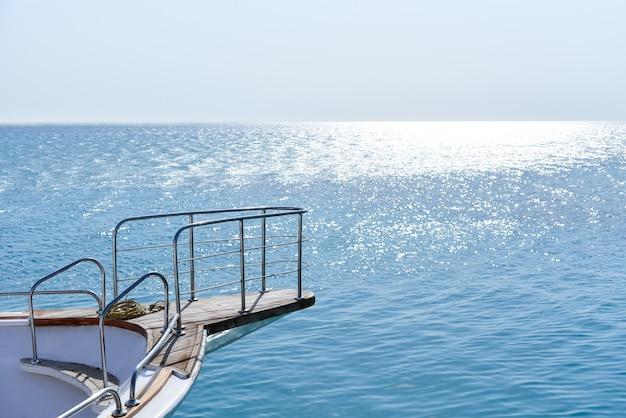 青い空を背景にした白いヨットの船首。 Premium写真