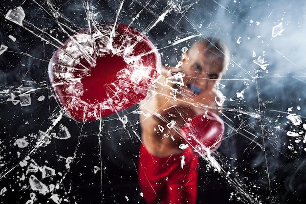 Боксер дробит стакан. молодой спортсмен по кикбоксингу на синем дыму Бесплатные Фотографии