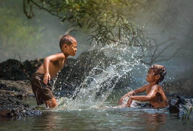 Мальчик друг счастливым смешно играет вода в потоке воды в сельской местности Premium Фотографии