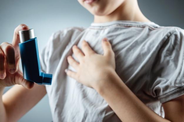 少年は、炎症性疾患、息切れを治療するために喘息吸入器を手に持っています。咳、アレルギー、気道疾患の治療の概念。 Premium写真