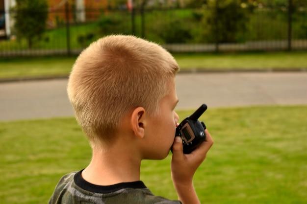 その少年はトランシーバーで話している。ボーイッシュな戦争ゲーム。 Premium写真